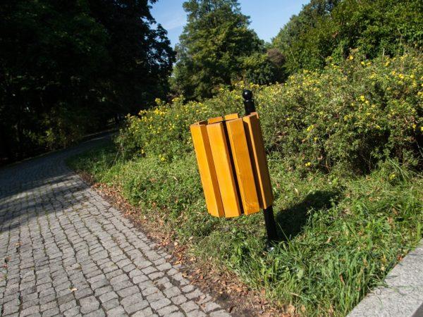 Kosz parkowy Genewa zdjęcie na tle roślin w parku malaarchitektura.info.pl