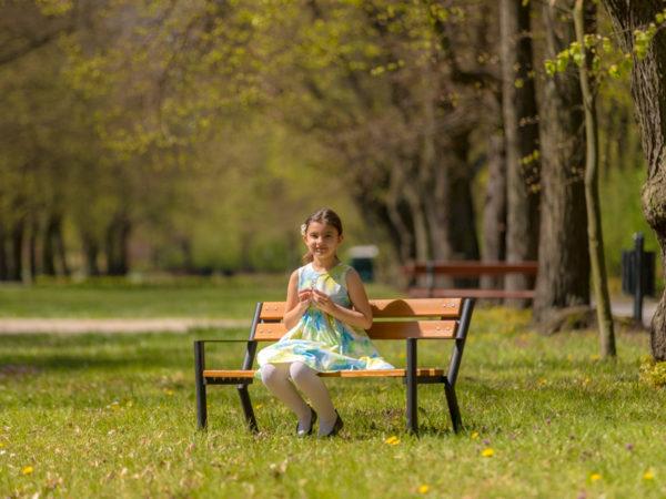Ławka dziecięca Śmiałek zdjęcie w parku z dziewczynką siedzącą na ławce malaarchitektura.info.pl