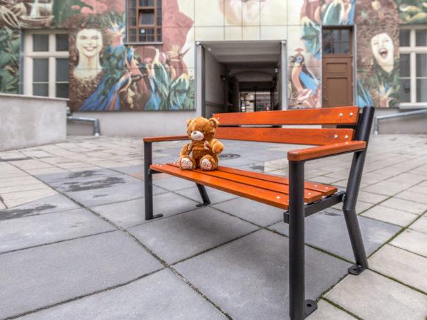 parkowa ławka dla dzieci Śmiałek z podłokietnikiem drewnianym zdjęcie na tle przedszkola malaarchitektura.info.pl