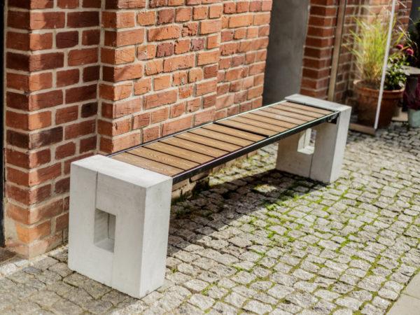 parkowa ławka betonowa Roma WPC bez oparcia zdjęcie na tle muru z cegieł malaarchitektura.info.pl