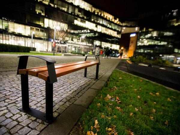 parkowa ławka stalowa Centurion bez oparcia zdjęcie nocą na tle galerii handlowej malaarchitektura.info.pl