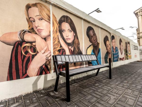 Parkowa ławka stalowa Gladiator WPC z podłokietnikiem zdjęcie na tle muralu malaarchitektura.info.pl