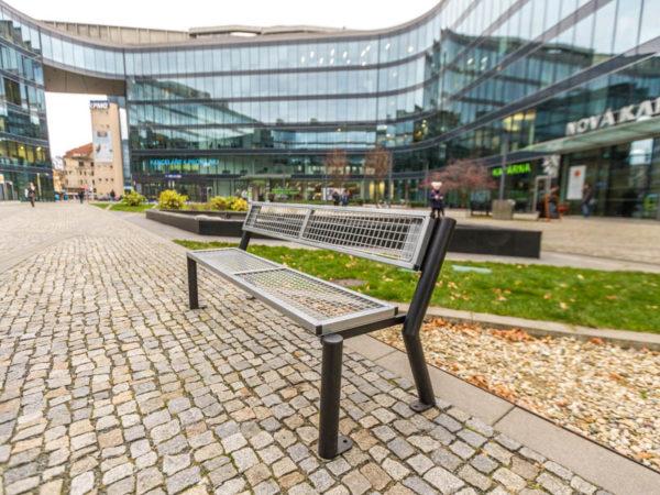 parkowa ławka stalowa Gladiator Solid zdjęcie na tle centrum handlowego malaarchitektura.info.pl