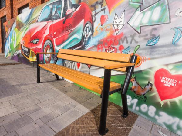 parkowa ławka stalowa Gladiator z podłokietnikiem drewnianym zdjęcie na tle graffiti z samochodem malaarchitektura.info.pl