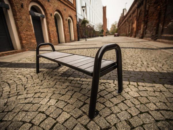 parkowa ławka stalowa Spartan WPC bez oparcia zdjęcie w industrialnym otoczeniu malaarchtektura.info.pl