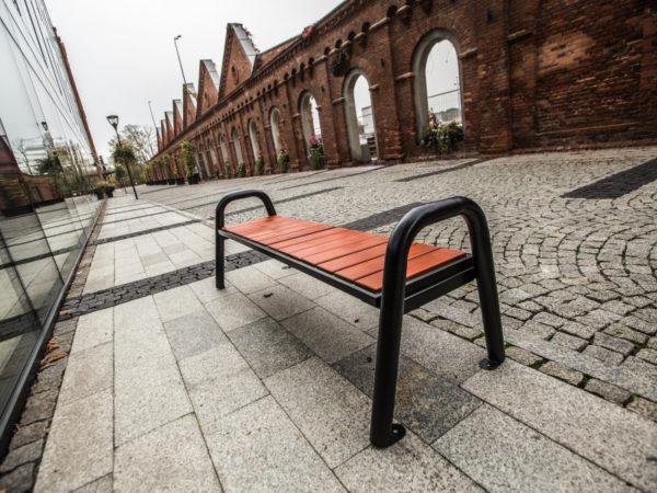 parkowa ławka stalowa Spartan Prestige bez oparcia zdjęcie w industrialnym otoczeniu malaarchitektura.info.pl