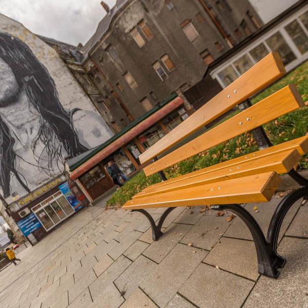 parkowa ławka żeliwna łódzka zdjęcie na tle muralu malaarchitektura.info.pl