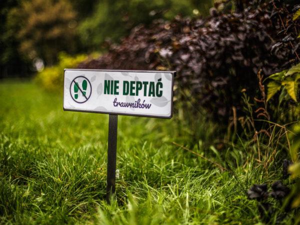 tabliczka informacyjna mała z naklejką nie deptać trawników zdjęcie na tle roślin malaarchitektura.info.pl